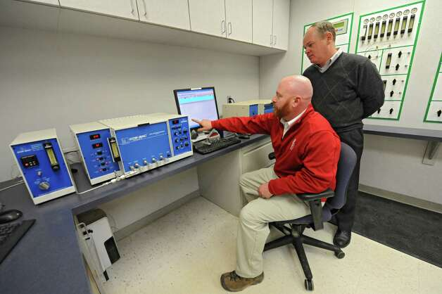 Lab Manager Marty Hogan, sitting, and Operations Manager Jeoff Delbridge perform gas analysis using the gas chromatograph in the new lab at Noble Gas Solutions on Thursday Dec. 18, 2014 in Albany, N.Y. Noble Gas Solutions provides gases to the nanotech sector among other companies and corporations.  (Lori Van Buren / Times Union) Photo: Lori Van Buren / 00029917A