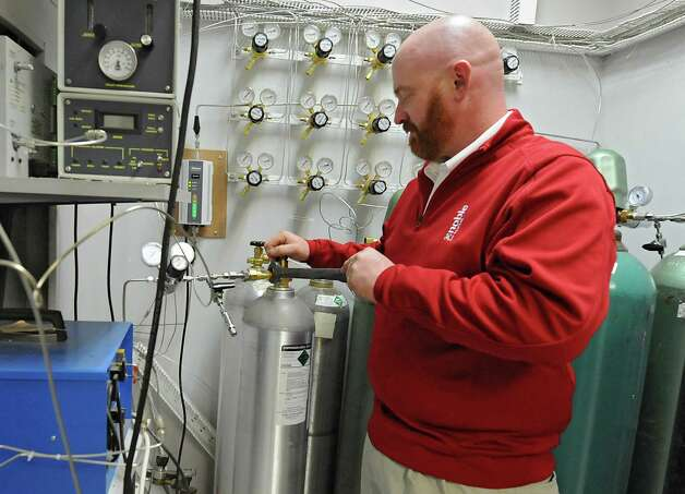 Lab Manager Marty Hogan connects a tank of gas to perform gas analysis using the gas chromatograph in the new lab at Noble Gas Solutions on Thursday Dec. 18, 2014 in Albany, N.Y. Noble Gas Solutions provides gases to the nanotech sector among other companies and corporations.  (Lori Van Buren / Times Union) Photo: Lori Van Buren / 00029917A