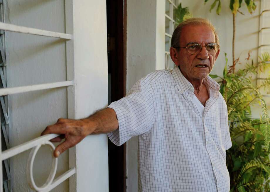 Rolando Sarraff stands at the entrance of his home in Havana, Cuba, Thursday, Dec. 18, 2014. A former intelligence official in the United States Thursday publically identified Rolando's son as the unnamed spy traded for three Cuban intelligence agents jailed in the United States, one who U.S. President Barrack Obama hailed as Washington's most valuable assets. But neither Cuban nor American officials have confirmed that Sarraff was spirited off the island and his parents have not heard from their son since he supposedly was freed. (AP Photo/Desmond Boylan) Photo: Desmond Boylan / Associated Press / AP