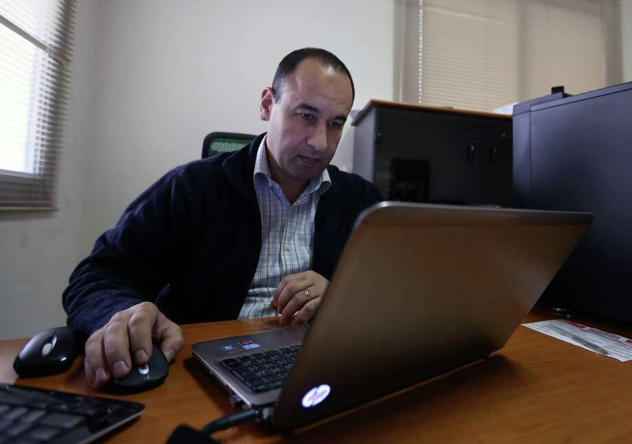 WITH STORY MIDEAST ISLAMIC STATE CYBERATTACK BY RAPHAEL SATTER - In this photo dated Wednesday, Dec. 17, 2014, Lebanese Bahaa Nasr of Cyber Arabs checks his email from his office in Beirut, Lebanon.  Cyber Arabs is an online safety project run by the London-based Institute for War and Peace Reporting and Nasr is among those who recently helped uncover a botched cyberattack suspected of having been carried out by the Islamic State group. (AP Photo/Bilal Hussein) Photo: Bilal Hussein / Associated Press / AP