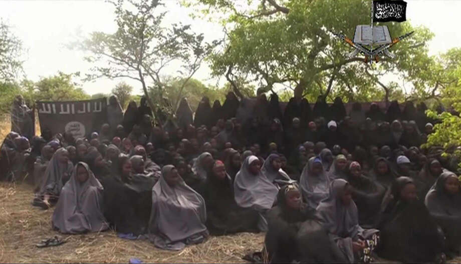 """FILE - This Monday May 12, 2014 file image taken from video by Nigeria's Boko Haram terrorist network, shows the alleged missing girls abducted from the northeastern town of Chibok. Islamic extremists killed 35 people and kidnapped at least 185, fleeing residents said Thursday of an attack near the town where nearly 300 schoolgirls were taken hostage in April. Teenager Aji Ibrahim said he was lucky to escape into the bushes. """"No doubt they were Boko Haram members because they were chanting """"Allahu akbar"""" (God is Great) while shooting at people and torching houses,"""" he told The Associated Press. (AP Photo/File) Photo: AP PHOTO / Associated Press / Militant Video"""