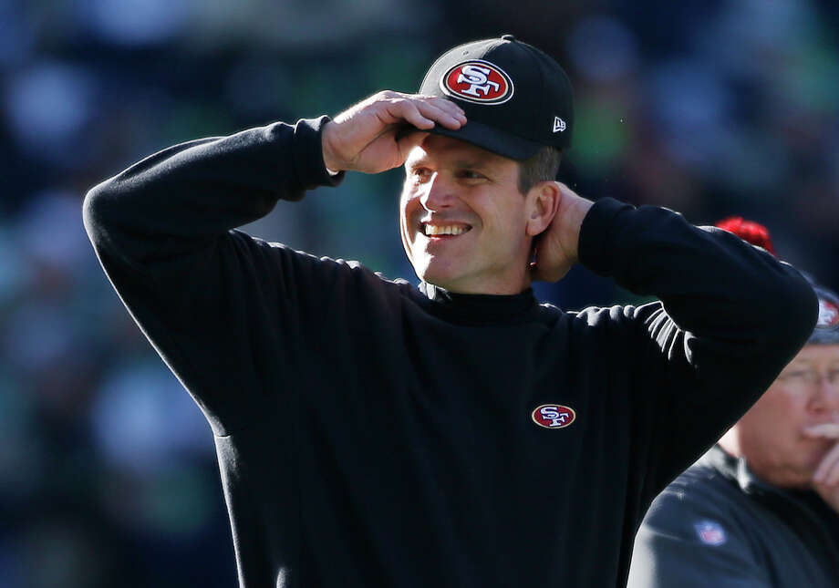 San Francisco 49ers head coach Jim Harbaugh adjusts his cap before an NFL football game against the Seattle Seahawks, Sunday, Dec. 14, 2014, in Seattle. (AP Photo/John Froschauer) Photo: John Froschauer / Associated Press / FR74207 AP
