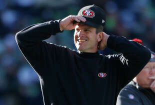 San Francisco 49ers head coach Jim Harbaugh adjusts his cap before an NFL football game against the Seattle Seahawks, Sunday, Dec. 14, 2014, in Seattle. (AP Photo/John Froschauer)
