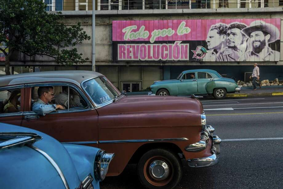 "Classic American cars, which Cubans have famously managed to keep in working condition for decades, and a poster that translates to ""All for the Revolution,"" on a street in Havana, Dec. 18, 2014. (Meredith Kohut/The New York Times) ORG XMIT: XNYT41 Photo: MERIDITH KOHUT / NYTNS"