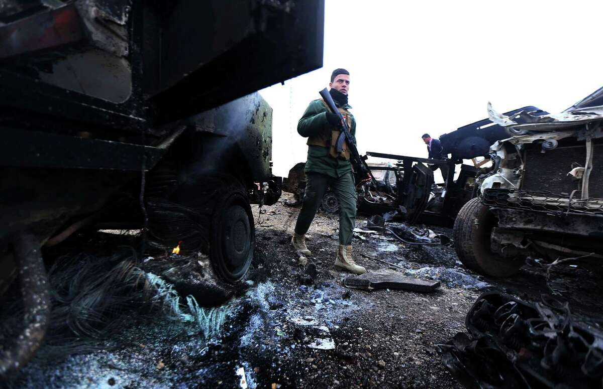 A Peshmerga fighter walks between burning vehicles following a suicide attack carried out by the Islamic State group in Kesarej village, south of to Zummar city, in the northern Iraqi Governorate of Nineveh, near the border with Syria on December 18, 2014. Kurdish forces backed up by US-led warplanes have recaptured a large area in Iraq near the Syrian border in an offensive this week against Islamic State jihadists, a US commander said. AFP PHOTO / SAFIN HAMEDSAFIN HAMED/AFP/Getty Images