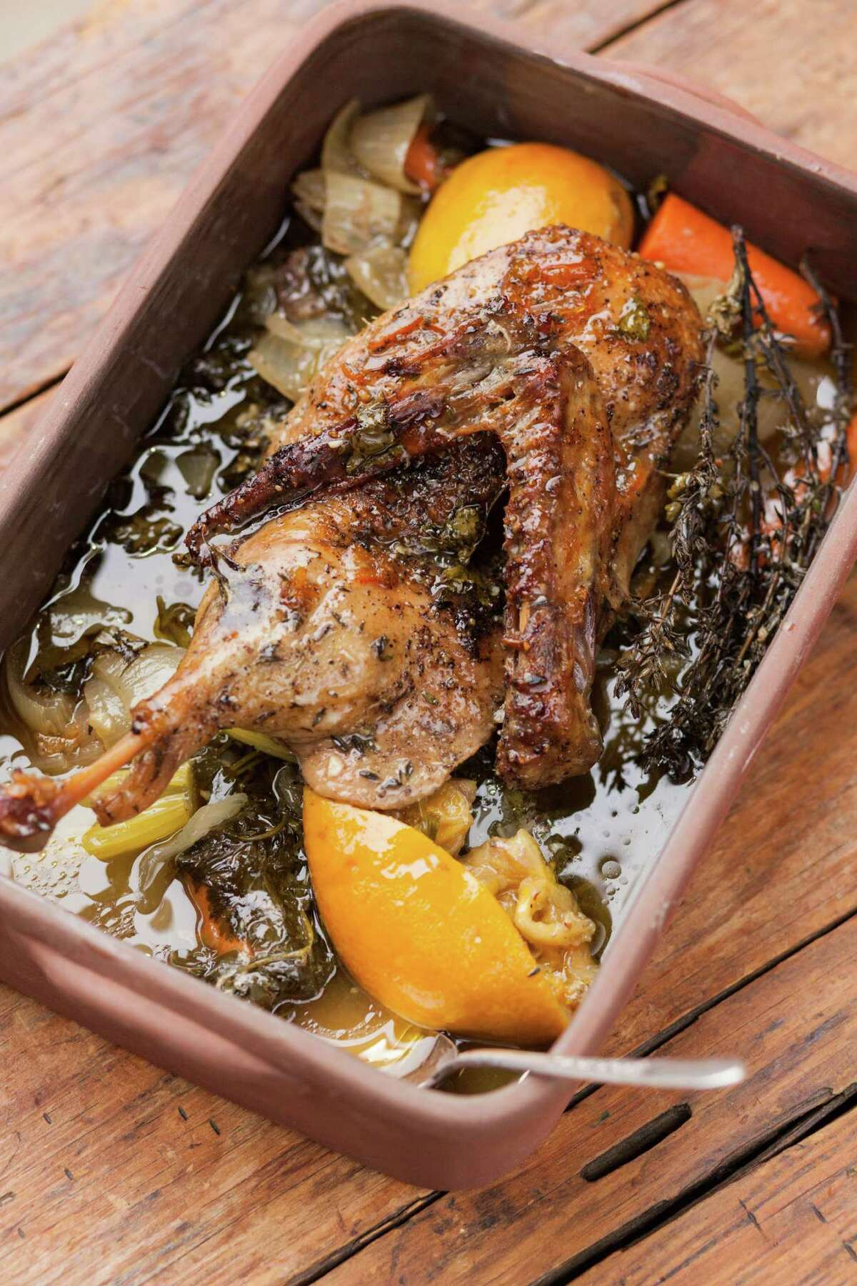 A deep pan is used to cook the duck with onions, carrots, celery, citrus, herbs and wine, allowing it to cook with all of the juices.