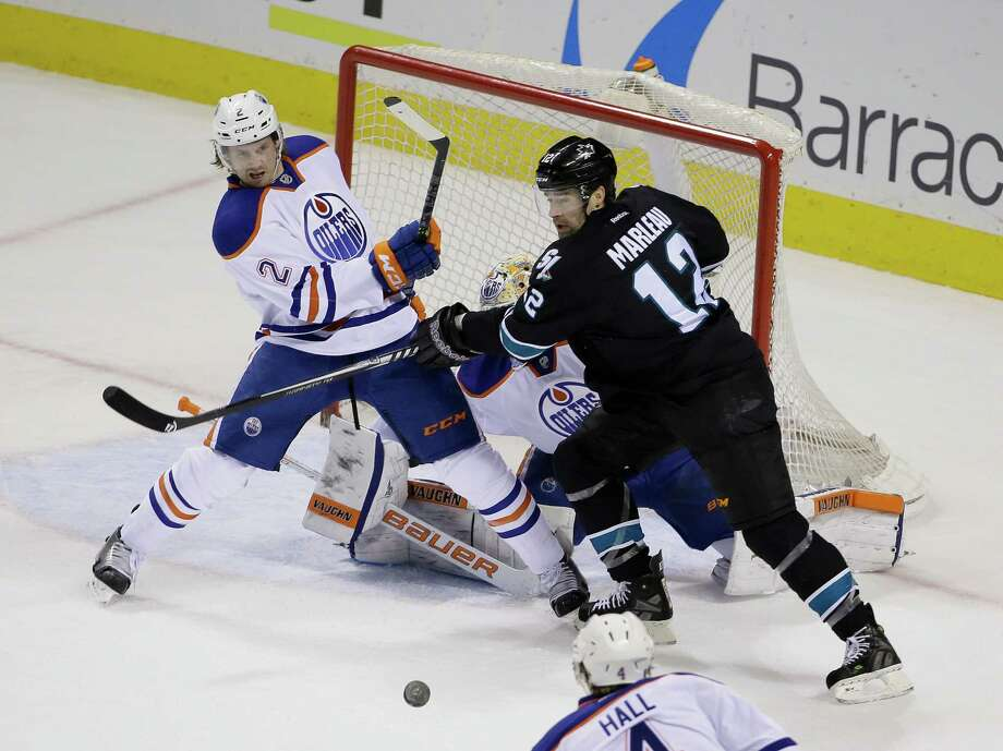 The Sharks' Patrick Marleau (right) goes for the puck against Edmonton defenseman Jeff Petry during the first period. Photo: Eric Risberg / Associated Press / AP