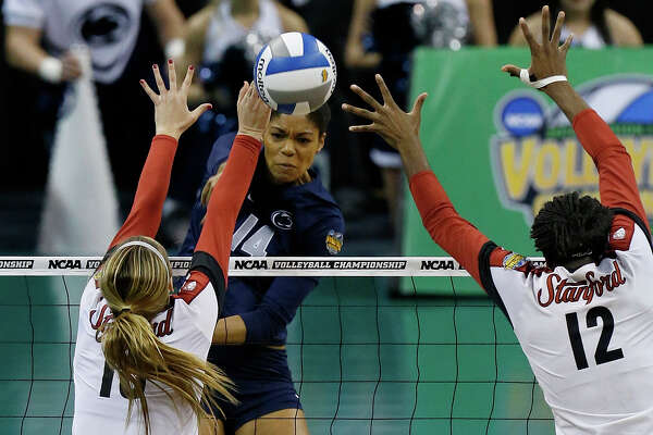 Penn State's Aiyana Whitney, center, hits past Stanford's Brittany Howard (16) and Inky Ajanaku (12) during an NCAA college volleyball tournament semifinal in Oklahoma City, Thursday, Dec. 18, 2014. (AP Photo/Sue Ogrocki)