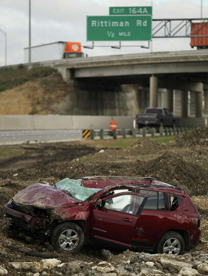A pickup truck (background) passes after a Jeep SUV rolled over off of the 4400 block of Interstate