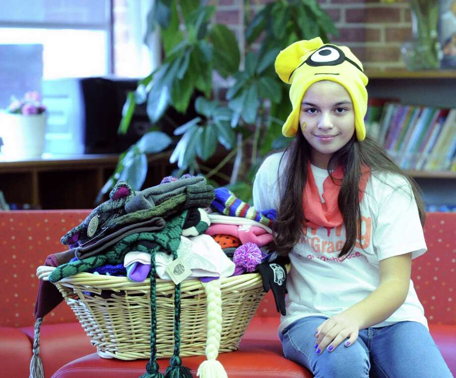 Stamford resdient, Grace Targonski, 11, a Dolan Middle School sixth grade student, with the 116 hats that she collected that were donated by Parkway School students and faculty to benefit pediatric cancer patients at the Smilow Cancer Hospital in New Haven, at the Parkway School in Greenwich, Conn., Friday, Dec. 12, 2014. Photo: Bob Luckey / Greenwich Time