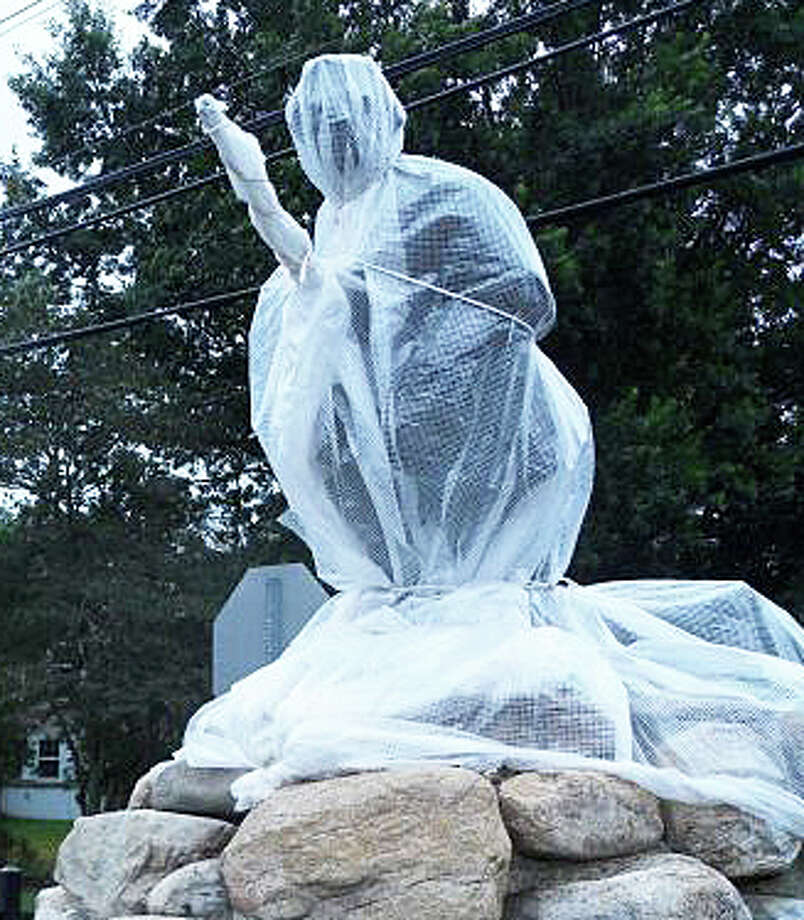 The Minute Man Monument, enshrouded for protection last fall during its restoration project, will be unveiled Monday. Photo: File Photo / Westport News