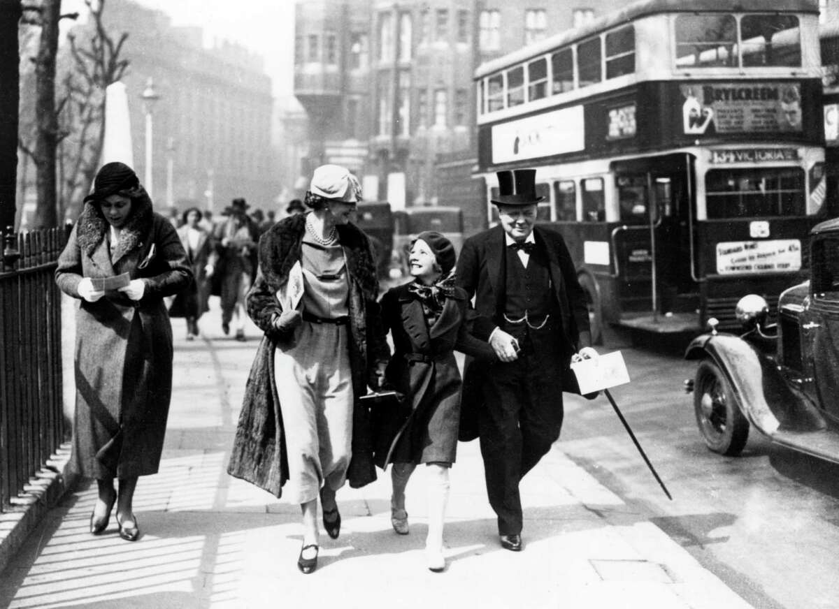 Clementine Churchill and her husband Winston walk hand in hand down a London street with their youngest daughter Mary(later Baroness Soames) Date: 9th May 1935.