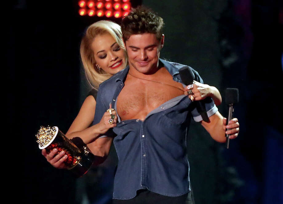 "Actor Zac Efron accepts the Best Shirtless Performance award for ""That Awkward Moment"" from singer Rita Ora onstage at the 2014 MTV Movie Awards at Nokia Theatre L.A. Live on April 13, 2014 in Los Angeles. Photo: Frederick M. Brown, Getty Images / 2014 Getty Images"