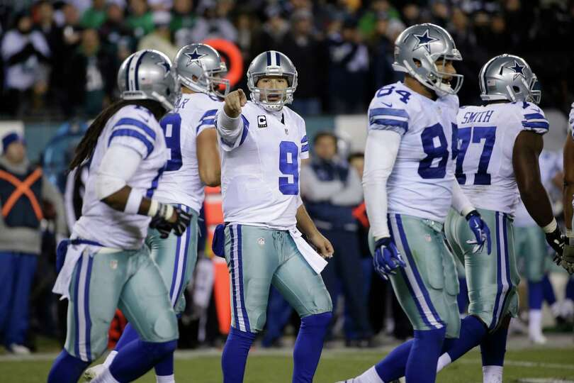 Cowboys quaterback Tony Romo points out directions to the offense during the second half against the