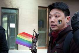 Yang Teng holds up a statue of the goddess of justice and a rainbow flag outside a Beijing court.