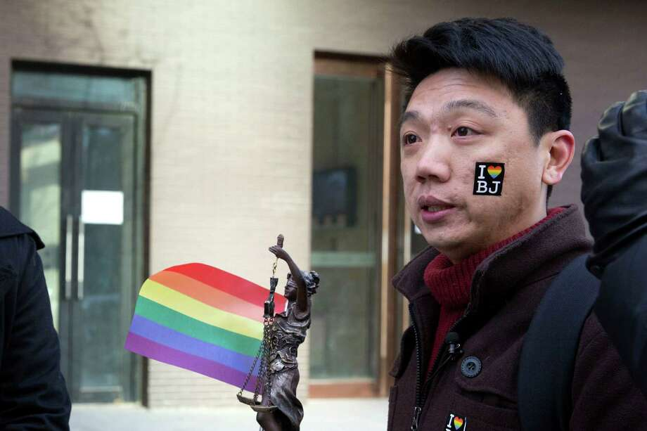 Yang Teng holds up a statue of the goddess of justice and a rainbow flag outside a Beijing court. Photo: Ng Han Guan / Associated Press / AP