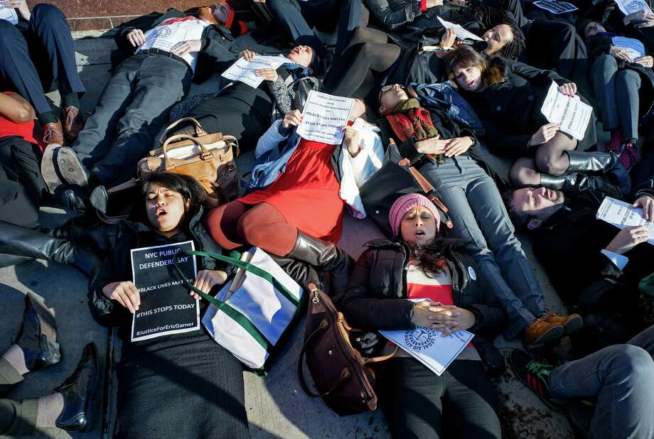 "Public defenders, members of the legal community and others lay down during a ""die-in""protest in the Brooklyn borough of New York Wednesday, Dec. 17, 2014.  A number of protests have been staged around the country following recent grand jury decisions not to indict white police officers in New York and Ferguson, Mo.,  over the deaths of unarmed black men.  (AP Photo/Craig Ruttle) ORG XMIT: NYCR101 Photo: Craig Ruttle / FR61802 AP"