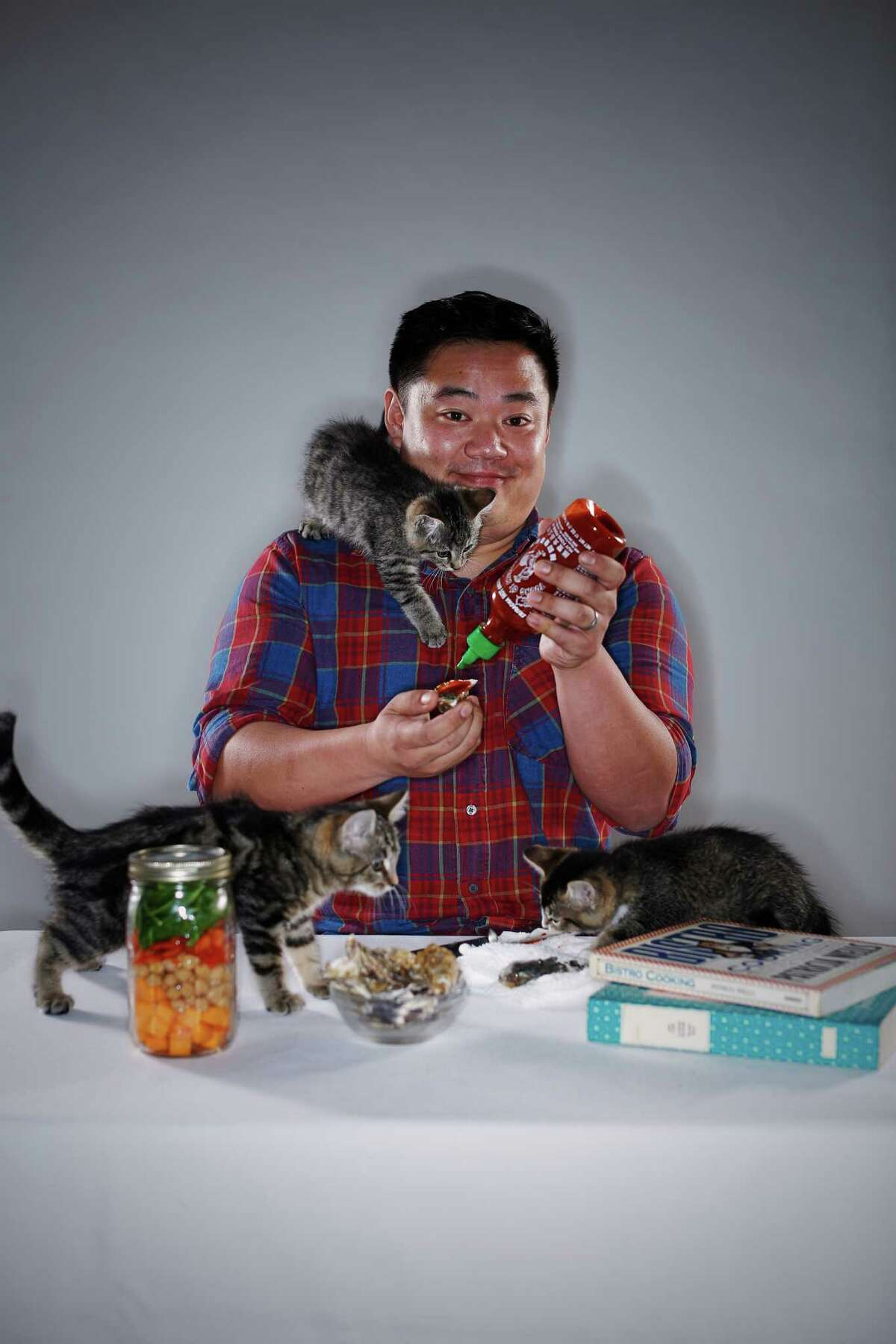 Lucky Peach editor Chris Ying gamely shows off this year's food trends. To represent cat cafes, volunteers from the San Francisco SPCA brought 2-month-old Pogo (left), Nerf and Frisbee to the photo shoot at The Chronicle. Each year the SPCA helps more than 5,000 animals find loving homes.Learn more and view available animals at www.sfspca.org/adopt.