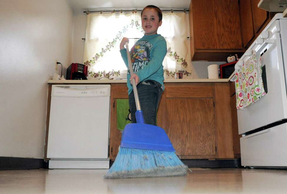 Stephanie Schultz's 6-year-old son helping with chores around their home on Friday Dec. 12, 2014 in Watervliet , N.Y. (Michael P. Farrell/Times Union)