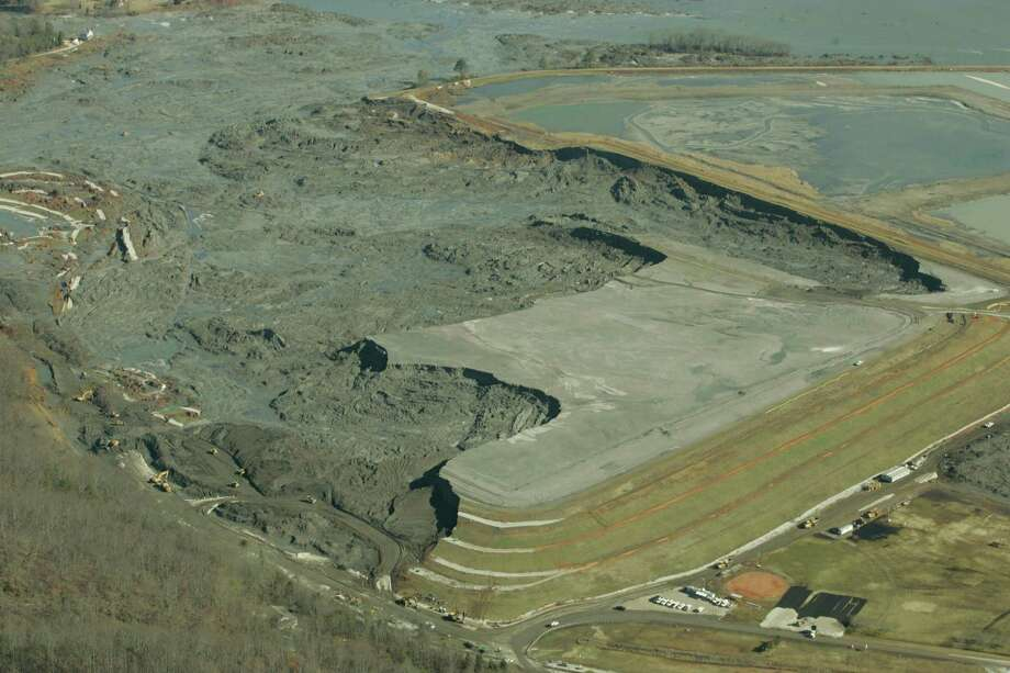 F ILE - In this Monday, Dec. 29, 2008 file image provided by Greenpeace, coal ash slurry left behind in a containment pond near the Tennessee Valley Authority's Kingston Fossil Plant is shown  in Harriman, Tenn., after the dyke at left broke Dec. 22, 2008. The Obama administration is under court order to unveil the rule Friday, Dec. 19, 2014 ending a six-year effort that began after the massive spill at the Tennessee power plant in 2008. Since then, the Environmental Protection Agency has documented coal ash waste sites tainting hundreds of waterways and underground aquifers in numerous states with heavy metals and other toxic contaminants. (AP Photo/Greeenpeace, Wade Payne) Photo: Wade Payne / Associated Press / Greenpeace
