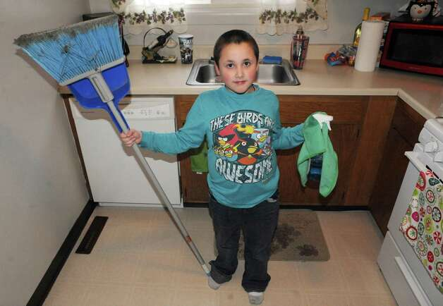 Stephanie Schultz's 6-year-old son helping with chores around their home on Friday Dec. 12, 2014 in Watervliet , N.Y.  (Michael P. Farrell/Times Union) Photo: Michael P. Farrell / 00029813A