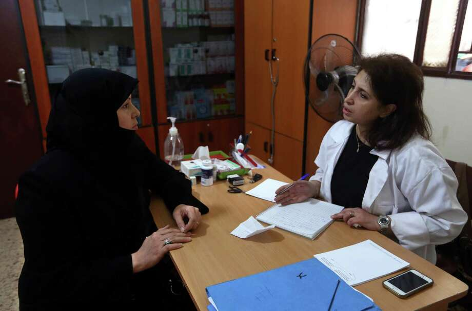 In this Wednesday, Dec. 10, 2014 photo, Hoda Barakat, right, a registered midwife, speaks with Syrian Wafaa Daaboul, 45, at a natal clinic in Beirut, Lebanon. Nearly 30,000 Syrian children born as refugees in Lebanon are in a legal limbo, not registered with any government, exposing them to the risk of a life of statelessness deprived of basic rights. (AP Photo/Bilal Hussein) Photo: Bilal Hussein / Associated Press / AP