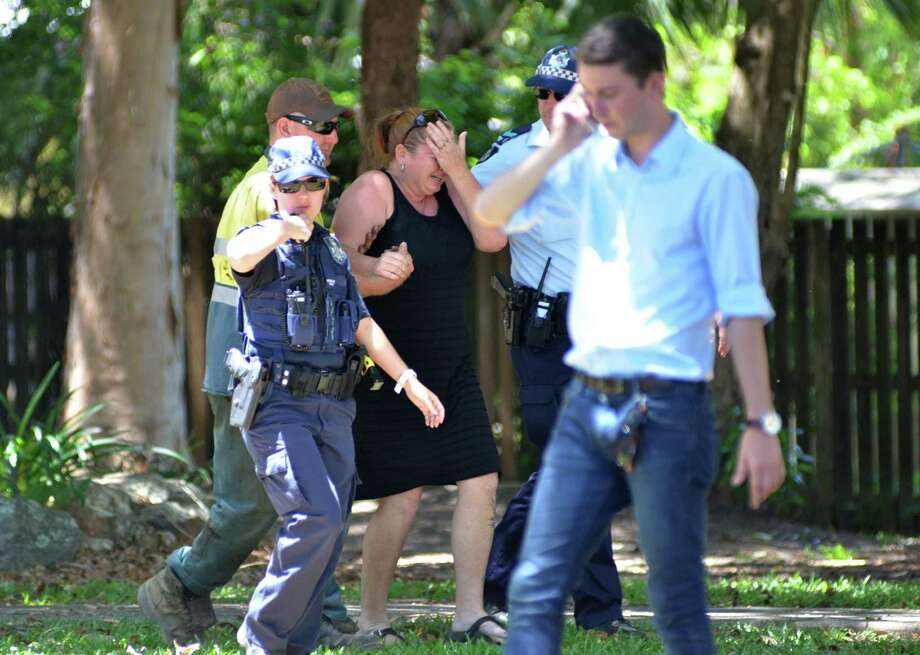 Police comfort a distressed woman at the scene where eight children aged between 18 months and 15 years were found dead at a home in the northern Australian city of Cairns, police said. Photo: ISAAC EGAN / AFP/Getty Images / AFP