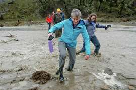 US Secretary of the Interior Sally Jewell crosses a swollen stream along the Red Bud trail in the Cache Creek Natural area & California State Wildlife area, near Williams, Calif., as seen on Friday Dec. 19, 2014. Bill 1025 sponsored by Representative Mike Thompson, D-CA 5th District, would protect 350,000 acres of public land in the proposed Berryessa Snow Mountain National Conservation Area.