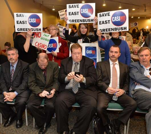 Representatives of the Howes Cavern casino site, bottom, and opponents of the East Greenbush casino site await the New York Gaming Facility Location Board's choices of casino sites during a meeting Wednesday Dec. 17, 2014, in Albany, NY.   (John Carl D'Annibale / Times Union) Photo: John Carl D'Annibale, Albany Times Union