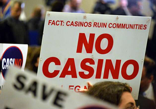 Casino opponents wave signs as they wait for the beginning of the New York Gaming Facility Location Board's  meeting Wednesday Dec. 17, 2014, in Albany, NY.   (John Carl D'Annibale / Times Union) Photo: John Carl D'Annibale, Albany Times Union