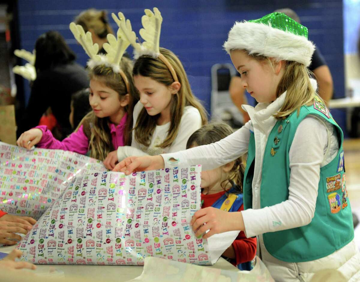 From left, Jenna Petrellese, 8, Emerson Davis, 8, and Bronwyn Hyland, 10, wrap gifts for a special service project that their Girl Scout Troop at St. Gregory the Great School is participating in, Friday, Dec. 19, 2014.