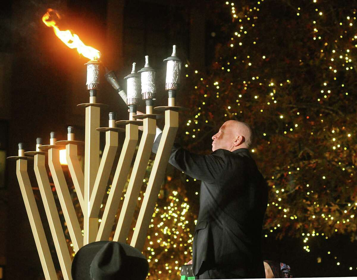 U.S. Representative Kevin Brady, of The Woodlands, lights the Shamash, the candle that is used to light the other eight candles, during the lighting of a nine foot candelabra Menorah at Market Street Central Park. Rabbi Mendel Blecher, of Chabad of The Woodlands, led the lighting of the Menorah.