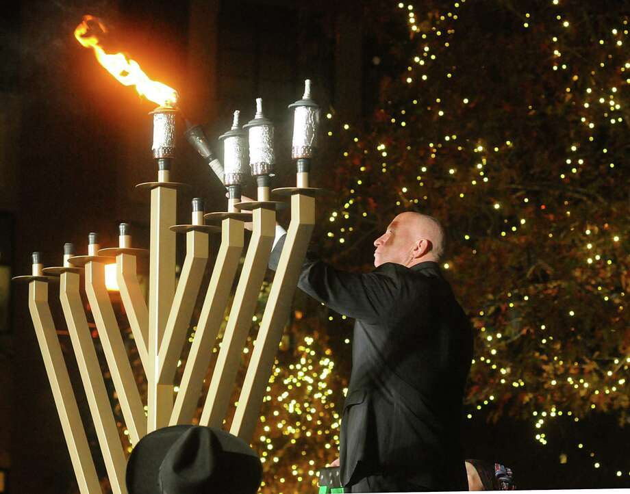 U.S. Representative Kevin Brady, of The Woodlands, lights the Shamash, the candle that is used to light the other eight candles, during the lighting of a nine foot candelabra Menorah at Market Street Central Park. Rabbi Mendel Blecher, of Chabad of The Woodlands, led the lighting of the Menorah. Photo: David Hopper, Freelance / freelance