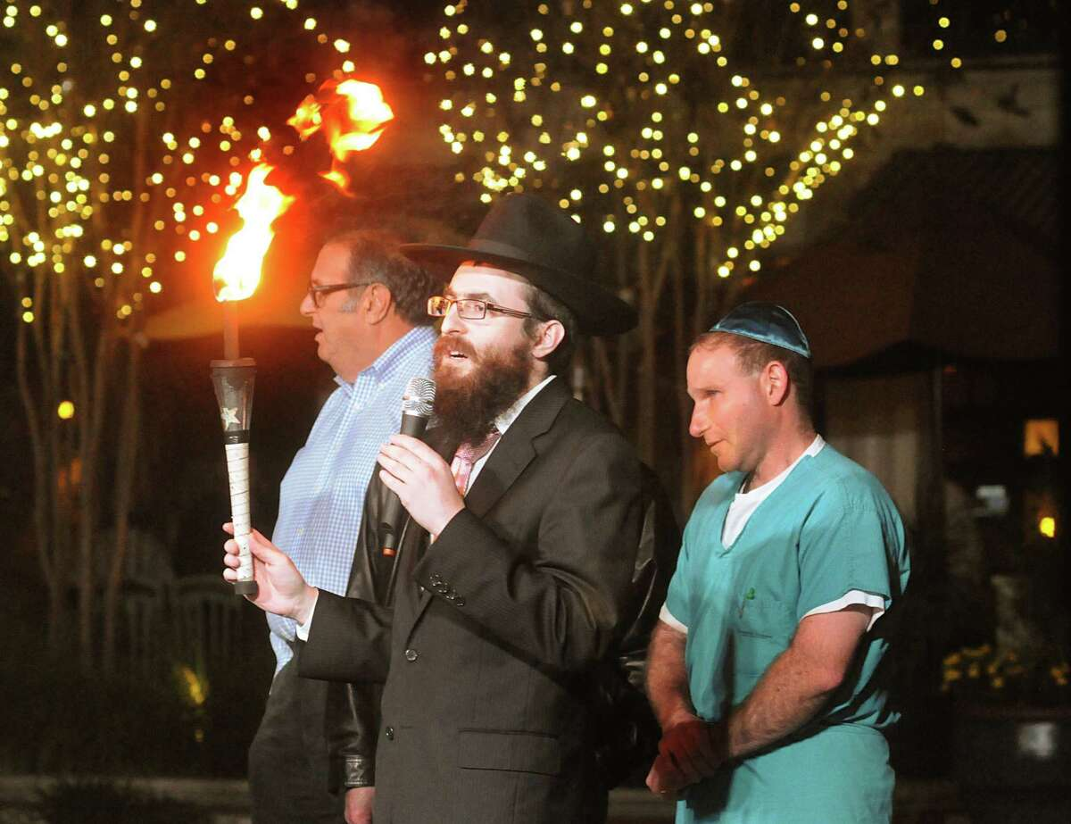 Rabbi Mendel Blecher holds the torch to be used during the lighting of a nine foot candelabra Menorah at Market Street Central Park. Rabbi Mendel Blecher, of Chabad of The Woodlands, led the lighting of the Menorah.