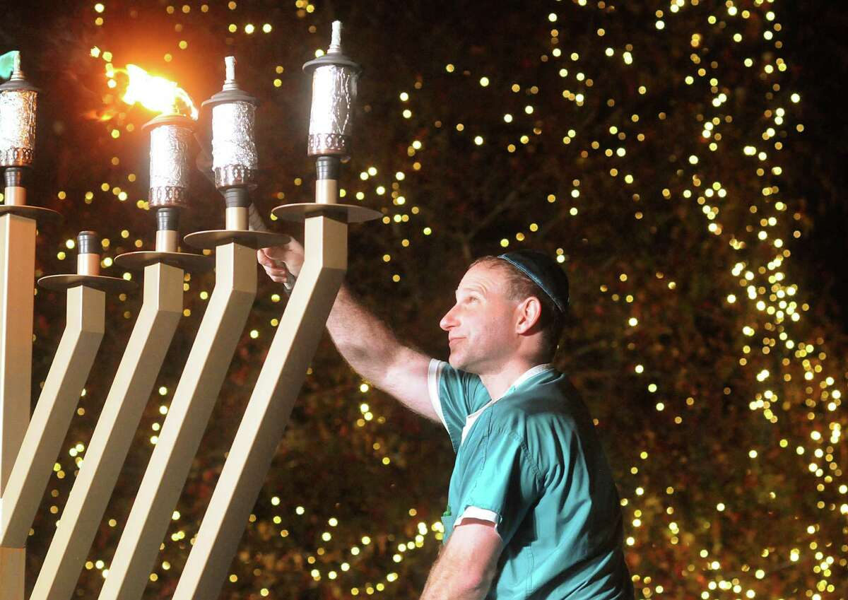Doctor Michael Gordeon, of The Woodlands, lights a candle during the lighting of the nine foot candelabra Menorah at Market Street Central Park. Rabbi Mendel Blecher, of Chabad of The Woodlands, led the lighting of the