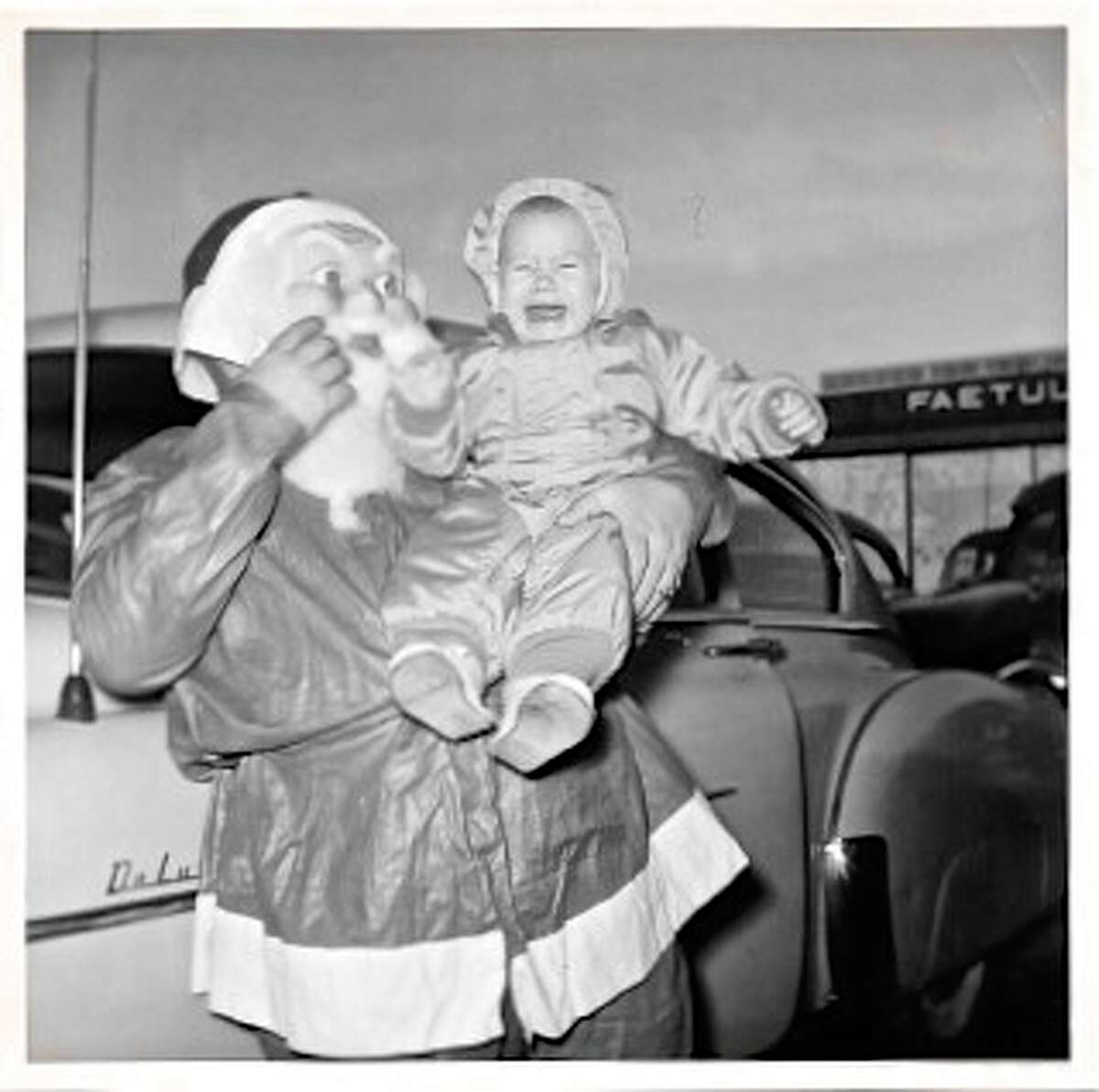 My mom took this photo of me in 1954, so the tradition of thrusting small children into the arms of strange Santas goes back at least that far. ;) And based on the film, A Christmas Story, it was happening in the 40s too. My dad was a Navy pilot flying anti-submarine missions during the Korean Conflict. One of the officers had dressed up as Santa, in a cheap plastic suit with a horrible plastic mask, and was headed in to a Christmas party to give out gifts. Guess my mom couldn't wait for the actual party to have me meet Santa.