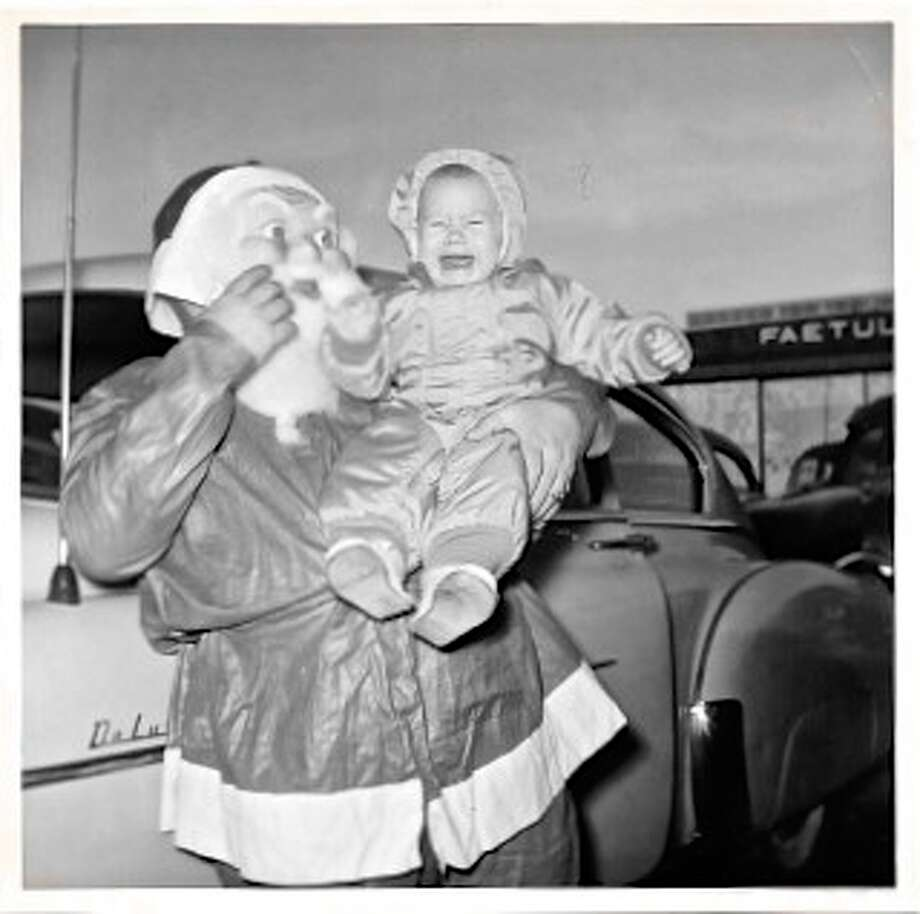 My mom took this photo of me in 1954, so the tradition of thrusting small children into the arms of strange Santas goes back at least that far.  ;)  And based on the film, A Christmas Story, it was happening in the 40s too.My dad was a Navy pilot flying anti-submarine missions during the Korean Conflict. One of the officers had dressed up as Santa, in a cheap plastic suit with a horrible plastic mask, and was headed in to a Christmas party to give out gifts. Guess my mom couldn't wait for the actual party to have me meet Santa.