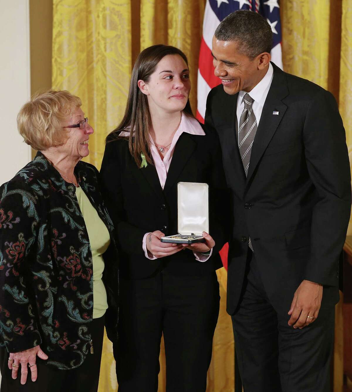 """President Barack Obama presents Erica and Cheryl Lafferty with the 2012 Presidential Citizens Medal, the nation's second-highest civilian honor, on behalf of their mother and daughter Dawn Lafferty Hochsprung in the East Room of the White House February 15, 2013 in Washington, DC. Principal Dawn Lafferty Hochsprung was killed during a mass shooting that left 26 people dead at Sandy Hook Elementary School in December 2012. """"Their selflessness and courage inspire us all to look for opportunities to better serve our communities and our country,"""" Obama said about this year's recepients."""