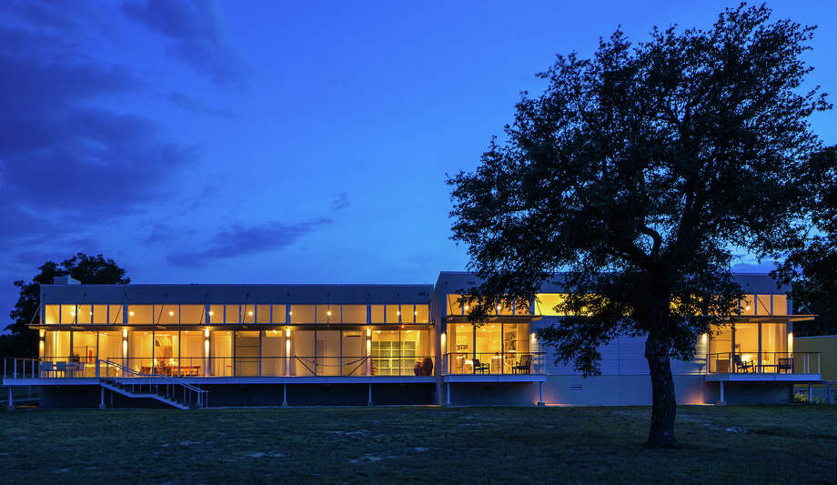The Boerne house architect Bill Lacy designed for him and his wife, Jane Stieren Lacy, glows at dusk. New York photographers John Bigelow Taylor and Dianne Dubler visited the house at Dog Leg Ranch over a year to document the home, its owners and the land in a limited-edition book commissioned by the Lacys. Photo: Courtesy John Bigelow Taylor + Dianne Dubler