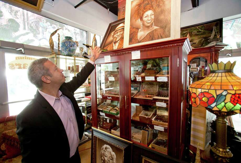 In this Thursday, Dec. 18, 2014 photo, Roberto Ramos, president of the Cubaocho Art and Research Center in Miami's Little Havana neighborhood, shows off a painting of the late Cuban-American salsa singer Celia Cruz painted on Cuban tobacco leaves. The Cuban cigar is set to make its first legal appearance in the United States in years, with relaxed guidelines allowing travelers to return with a few of the once-forbidden items in their suitcases. But the cigars won't roll into stores just yet, and owners say they aren't worried about business. (AP Photo/Wilfredo Lee) ORG XMIT: FLWL208 Photo: Wilfredo Lee / AP
