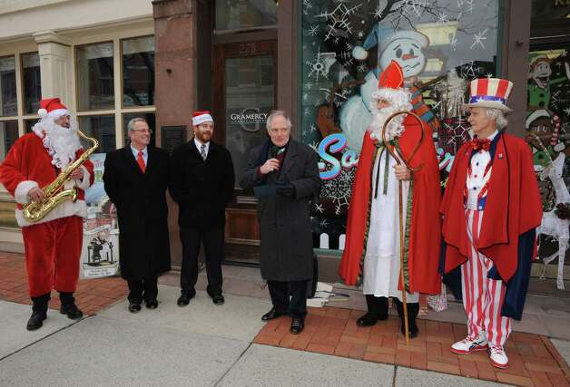"""Left to right, Luke Sax-O-Clausa€ McNamee, Mayor Lou Rosamilia,Duncan Crary, Jack Casey, Sinterklass a.k.a. St. Nicholas Karl Felsen and Uncle Sam Fred Polnisch proclaim """"Henry Livingston Jr. Day"""" to be Dec. 23, 2014 in Troy, in honor of the surprise jury verdict after the Dec. 7 """"Trial Before Christmas,"""" held in the Rensselaer County Courthouse in front of Some Girls Boutique on Friday Dec. 19, 2014 in Troy ,N.Y.  (Michael P. Farrell/Times Union) Photo: Michael P. Farrell / 00029936A"""