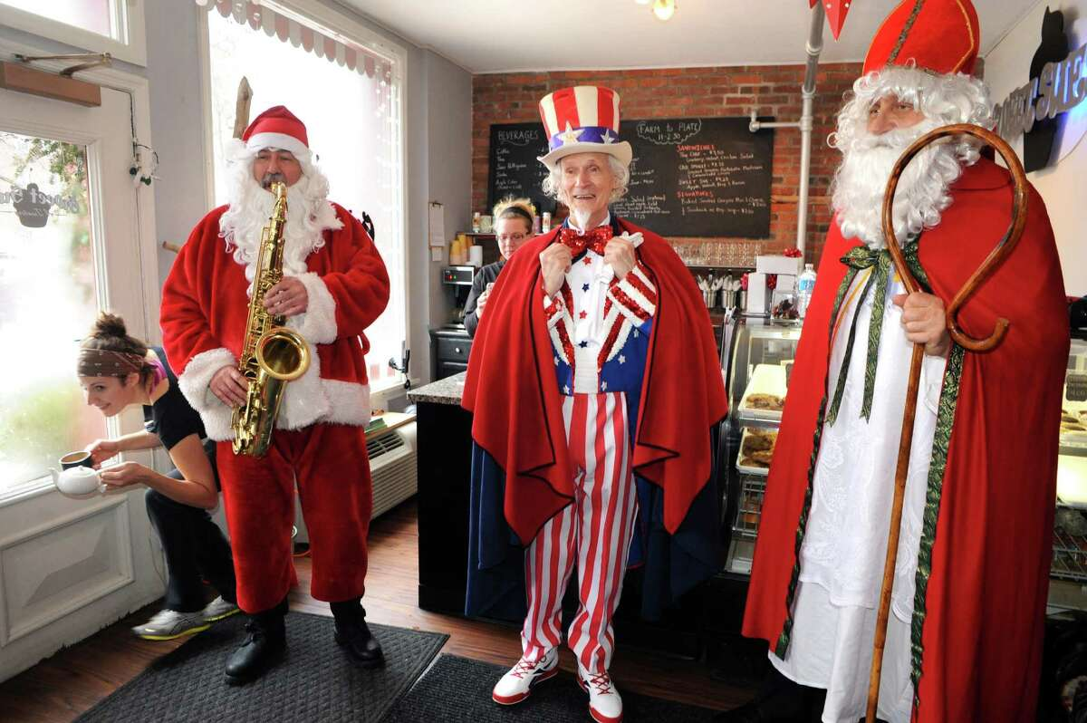 Luke Sax-O-Clausa€ McNamee, left, Uncle Sam Fred Polnisch and Sinterklass a.k.a. St. Nicholas Karl Felsen visit Sweet Sue's on Friday Dec. 19, 2014 in Troy ,N.Y. (Michael P. Farrell/Times Union)