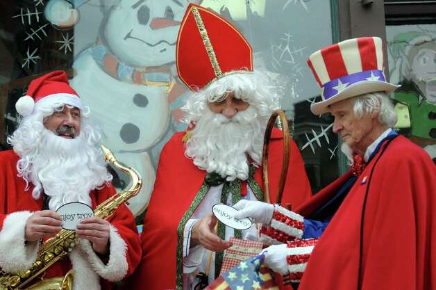 """Luke Sax-O-Clausa€ McNamee, left,  Sinterklass a.k.a. St. Nicholas Karl Felsen and Uncle Sam Fred Polnisch give each other gifts  as  """"Henry Livingston Jr. Day"""" was proclaimed to be Dec. 23, 2014 in Troy, in honor of the surprise jury verdict after the Dec. 7 """"Trial Before Christmas,"""" held in the Rensselaer County Courthouse in front of Some Girls Boutique on Friday Dec. 19, 2014 in Troy ,N.Y.  (Michael P. Farrell/Times Union) Photo: Michael P. Farrell / 00029936A"""