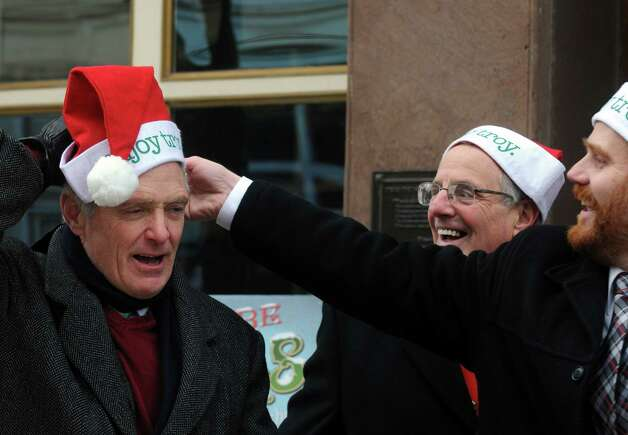 "Jack Casey,, left, Mayor Lou Rosamilia and Duncan Crary put on enjoy Troy Santa hats as ""Henry Livingston Jr. Day"" is  proclaimed to be Dec. 23, 2014 in Troy, in honor of the surprise jury verdict after the Dec. 7 ""Trial Before Christmas,"" held in the Rensselaer County Courthouse in front of Some Girls Boutique on Friday Dec. 19, 2014 in Troy ,N.Y.  (Michael P. Farrell/Times Union) Photo: Michael P. Farrell / 00029936A"