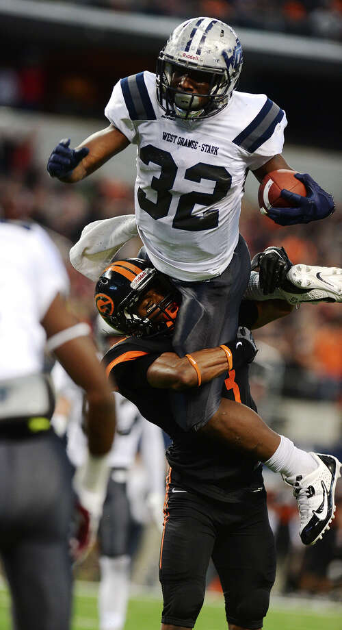 West Orange-Stark's Trey Baldwin, No. 32, attempts to vault over Gilmer's Devin Smith, No. 3, during Friday's championship game. The West Orange-Stark Mustangs played the Gilmer Buckeyes for the 4A Division II championship title Friday at AT&T Stadium in Arlington, Texas.  Photo taken Friday 12/19/14  Jake Daniels/The Enterprise Photo: Jake Daniels / ©2014 The Beaumont Enterprise/Jake Daniels