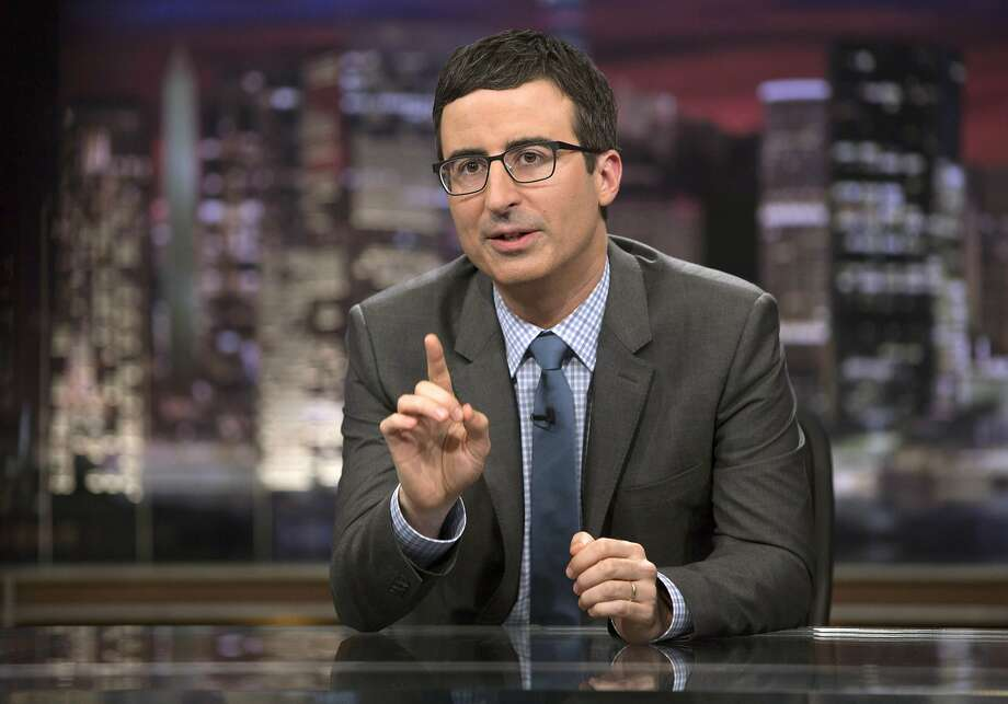 """In this April 2014 image released by HBO, host John Oliver speaks during """"Last Week Tonight with John Oliver,"""" in New York. Oliver, who subbed for Jon Stewart as host of """"The Daily Show"""" last summer and began his own HBO weekly show in April, often devotes about half of his 30 minutes to a single topic below the headlines. His subsequent report questioning the pageant's scholarship program was the latest example of how Oliver has quickly moved beyond his roots at """"The Daily Show"""" to produce something distinctive, and usually hilarious. (AP Photo/HBO, Eric Liebowitz) Photo: Eric Liebowitz, Associated Press"""