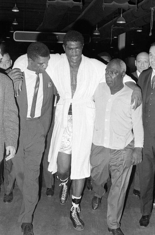 FILE - In this Feb. 6, 1967, file photo, unidentified handlers assist Ernie Terrell back to his dressing room after his 15-round heavyweight title fight with Muhammad Ali in Houston, Texas. Terrell, whose brief reign as heavyweight champion ended with a punishing loss to Muhammad Ali in a 1967 grudge match, died Tuesday, Dec. 16, 2014, in Chicago. He was 75.  (AP Photo/File)  ORG XMIT: NY172 Photo: Anonymous / AP