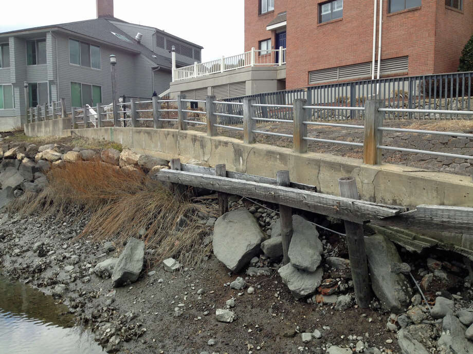 A crumbling seawall at 3 River Road in Cos Cob is being deemed a safety hazard by town leaders, who are filing a lawsuit to compel repairs. Photo: Robert Marchant, Anne W. Semmes / Greenwich Time
