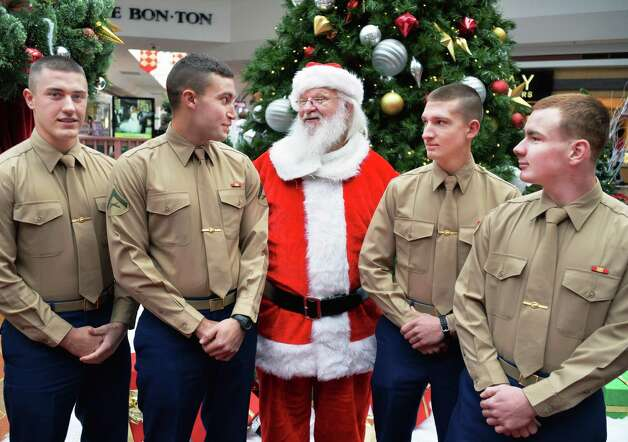 US Marines home on Christmas leave, from left, PFC Robert Murray of Hartford, Vt., LCPL Nick Harrington of Saratoga Springs, PVT Luke Russell of Jacksonville, VT. and PVT Charles Whittemore of Rutland, Vt. pose for a photo with Santa at the Wilton Mall Friday Dec. 19, 2014, in Wilton, NY.   (John Carl D'Annibale / Times Union) Photo: John Carl D'Annibale
