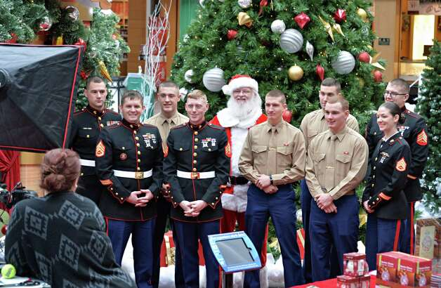 US Marine Corps members, in khaki shirts, home on Christmas leave, and members of the Marine Corps Recruiting sub-station in Saratoga Springs pose for a photo with Santa at the Wilton Mall Friday Dec. 19, 2014, in Wilton, NY.   (John Carl D'Annibale / Times Union) Photo: John Carl D'Annibale